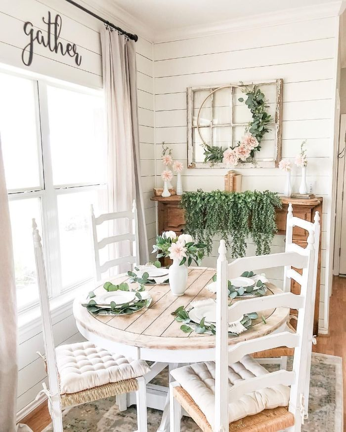 white cushions on chairs small round table farmhouse dining table greenery decorations