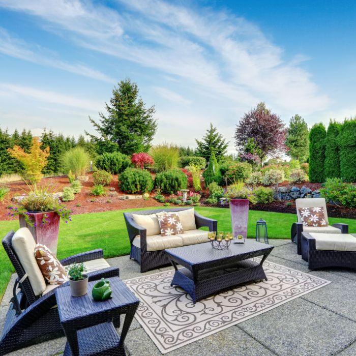 white cushions on rattan garden furniture placed on small rug backyard décor ideas