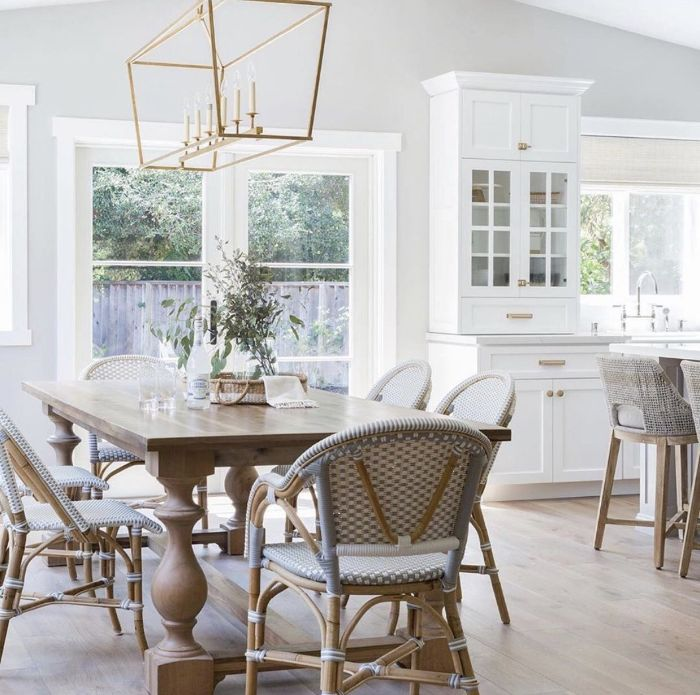 white walls and cupboards farmhouse kitchen table wooden chairs and large table chandelier hanging above it