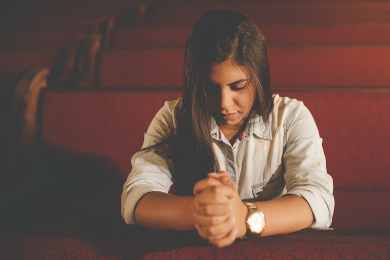 girl who is praying in the church quite time