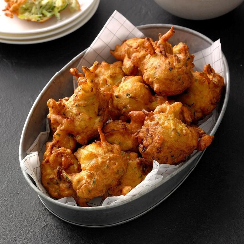 zucchini fritters in white bowl with napkin