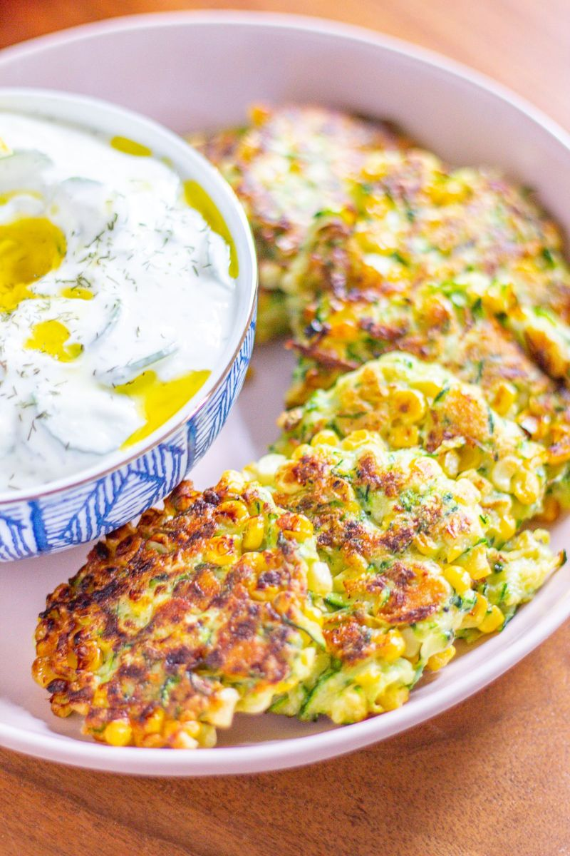 zucchini fritters recipe in white bowl with sauce