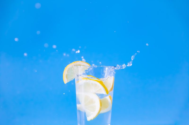 benefits of lemon water lemon slice splashing in water