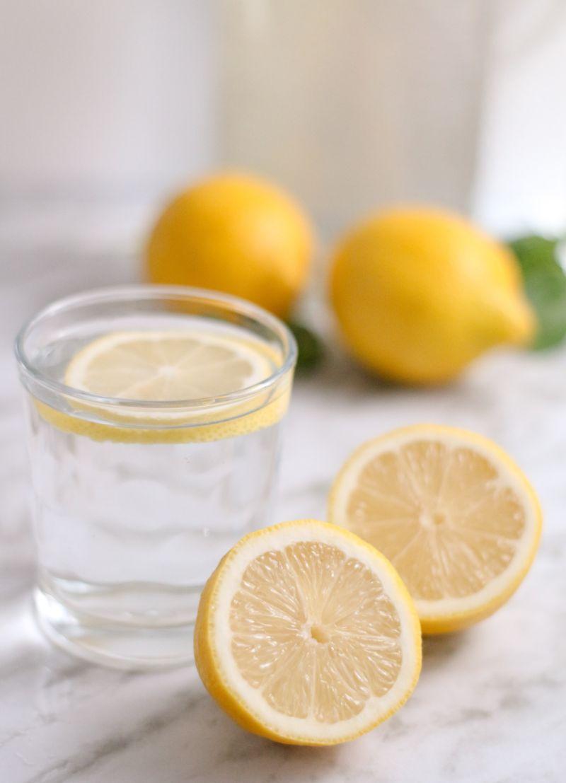 halved lemon benefits of lemon water glass of water