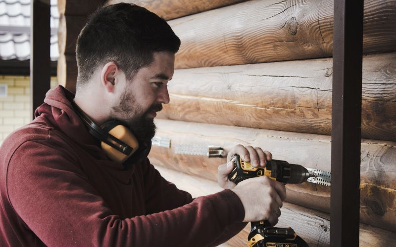 man drilling home improvements wearing headphones