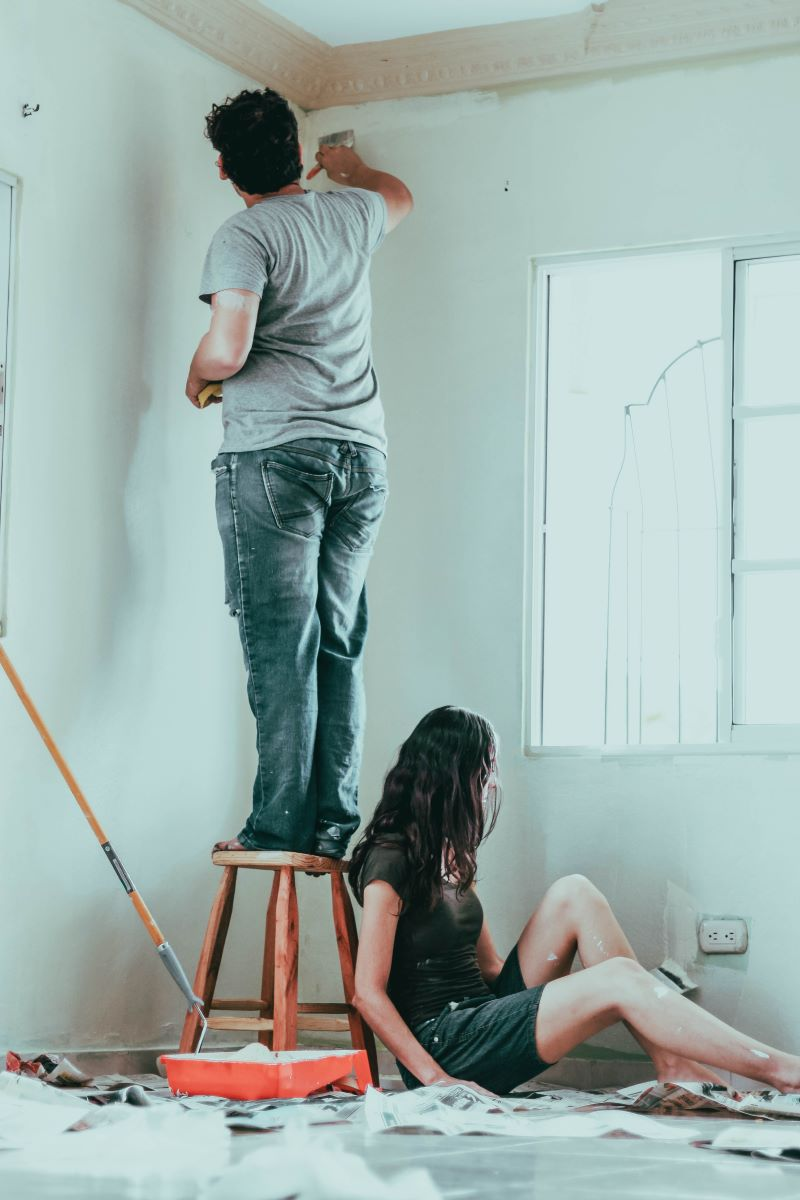 man on chair painting wall home improvements woman sitting on floor