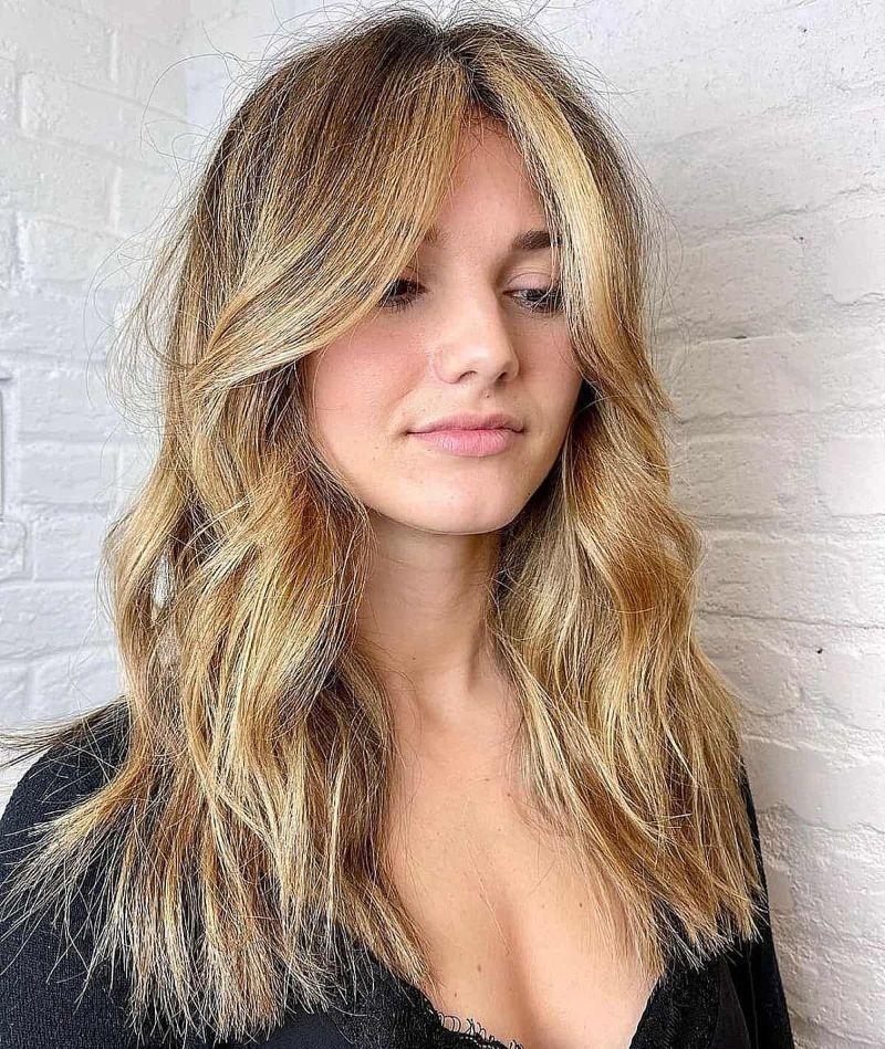 blonde woman curtain bangs curly hair