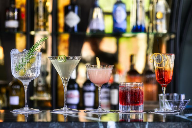 cocktail glasses gin drink recipes arranged on bar