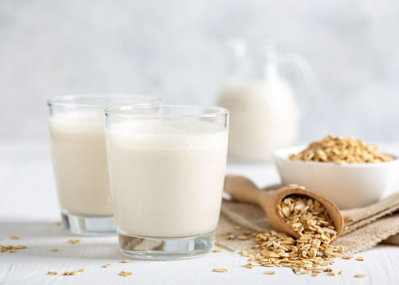 glasses jug filled with homemade oat milk