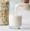 milk poured into glass homemade oat milk oats in jar