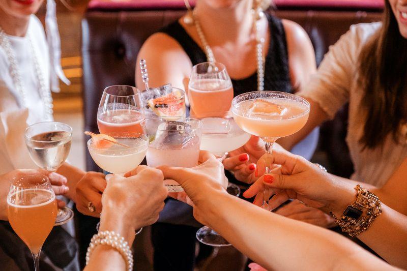 women making toast gin mixed drinks